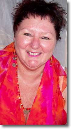 Photo of Teena Hughes March 2009, with handpainted silk in hot pink and orange.